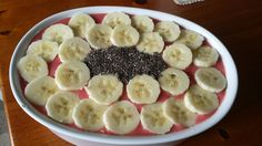 Smoothie bowl with bananas, pineapple and strawberries topped with banana and chia seeds.