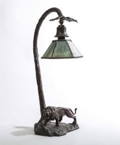 <b>ART NOUVEAU BRONZE PATINATED METAL LAMP</b> <br /> With prowling lion base and an associated green slag glass hexagonal shade. 20 1/2 x 9 in. <br />  <br /> The Estate of Sue Blair, Kansas City, MO <br />