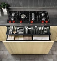 I need a stove top like that!! Including the cool red knobs!!! Natural Skin Kitchen by Minacciolo: Industrial and Sleek
