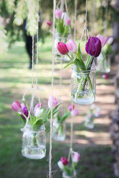 Des pots en verres de conserve, pour une cérémonie,  suspendu avec une ficelle, dans une allée, avec des couleurs de printemps, des tulipes multicolores .......