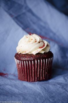 Red velvet cupcake on a bed sheet backdrop with natural window light. #foodphotography #cupcake #redvelvet