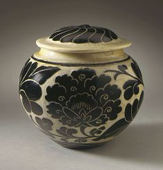 China, probably Henan Province  Lidded Jar (Guan) with Floral Scrolls, late Jin dynasty or early Yuan dynasty, about 1200-1300  Ceramic; Stoneware; Cizhou ware, Cizhou ware type, wheel-thrown stoneware with cream glaze and wax-resist and carved black overglaze decoration, Height: 4 7/8 in. (12.4 cm); Diameter: 5 in. (12.7 cm)