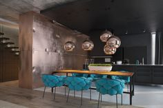 In the dining room and kitchen, however, we get a swift kick of color, starting with the turquoise cushioned dining chairs. While they somehow still feel Eames-inspired, the colorful pillowed design is decidedly more comfortable and the bright color goes oh-so-well with the neutral scheme.