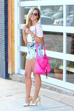 Overshorts with a lace crop top and a neon pink bucket bag and gold pumps