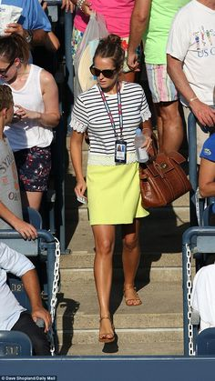 Kim wore a striped short-sleeved T-shirt and a vivid yellow skirt teamed with tan sandals and a match Burberry Bayswater handbag