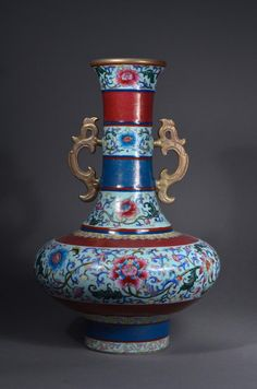 Chinese Famille Rose enameled porcelain vase; the unusually squat ovoid body features colourful enameled and prominent lotus blooms borne on an undulating vine with attendant offshoot buds; above and below the body features a register of imprinted gilt gold ruyi head designs reserved on red; the long neck features lotus blooms; alternating gilt gold designs reserved on blue and red: both bordered by a narrow double blue and red line; flared rim decorated with gilt gold with the interior in…