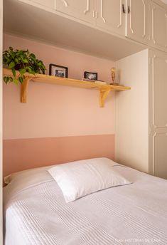 Quarto de casal com meia parede rosa tem cama entre armários embutidos e prateleira de pinus com planta e luminária. | A tour into a rented apartment decorated with simples ideias, colorful objects and fun vibe.
