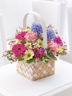 -Give their home an instant lift with this brightly coloured basket of gorgeous spring flowers. We've chosen a complementary mix of pink and cerise, lilac and lemon – it's all arranged perfectly and is ready to display in pride of place as soon as it arrives.<br /><br />Featuring 2 pink carnations, a light pink spray carnation, a cream spray chrysanthemum, 2 cerise freesia, 2 cerise germini and 2 blue hyacinths with eucalyptus, pittosporum and pink genista, presented in a two-tone interwoven…
