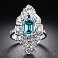 This bright and exuberant Art Deco dinner ring stars an unexpected gemstone - an electric turquoise blue emerald-cut zircon weighing 3.70 carats. This intriguing and and colorful gemstone radiates from the center of a sparkling, geometrically designed platinum and diamond dinner ring ablaze with 8 bright-white round brilliant cut diamonds totaling 1.00 carat. This fun, fancy, yet sophisticated, jewel, circa 1920's, measures 1 inch long by about 5/8 inch wide.