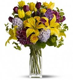 T148-1A Regular as shown $99: purple hydrangea and tulips, yellow spray roses, and even more tulips along with sunny asiatic lilies, lavender hyacinth plus green bupleurum and salal
