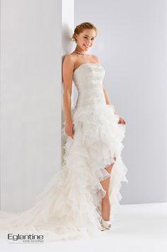 Robe de mariée en organza et dentelle, avec une jupe à volant courte devant et longue derrière. Boutonnage dos. Disponible en ivoire et en blanc