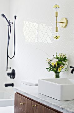 Crisp black and white bathroom with tiled walls, marble sink, wood cabinets, and small floral arrangement