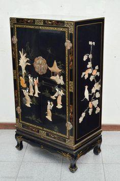 Armário japonês em madeira laqueada na cor preta. Duas portas, interior com uma prateleira. Parte ex