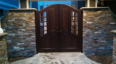 Designer Custom Wood Gate by Garden Passages. Double Gate with Raised Paneling, Decorative Wood Pickets, and Arched Crossbars