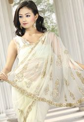 This off white net saree is embellished with stone, beads and zari work in floral motif all over the saree. The c-border of the saree with heavy embroidery makes the saree look more attractive. As shown blouse can be made available and also can be customized as per your style subject to fabric limitation. Slight variation in color and patch patti is possible.
