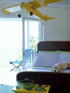 A model airplane hangs above the bed in this boy's room.