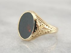 Handsome and sophisticated, this vintage ring was designed to be worn as a men's pinky ring, but is small enough for a ladies hand. Subtle Art Deco engravings frame the oval bloodstone at the center. Circa 1920s