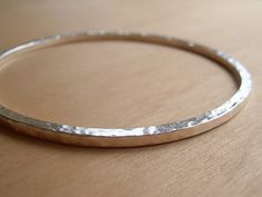 A lovely solid sterling silver bangle, hand forged from chunky square wire. It has been given a hammered texture and polished to a high shine finish.