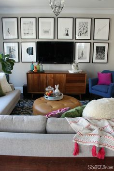 Love this cozy family room with TV gallery wall of black and white photos kellyelko.com #gallerywall #art #familyroom #homedecor