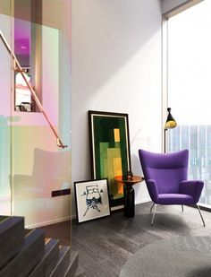 Living space with a purple statement armchair, a floor lamp, and a iridescent space separator
