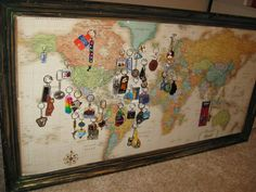 Keychains from across the world dispalyed on world map. Old framed picture found at thrift store repurposed as frame and backing for world map. Frame distressed and painted to look aged like driftwood. Cork board glued to picture holds push pins to hang the keychains on. World map cut to size and glued onto corkboard with spray adhesive. String is used to link keychains to smaller locations on the map.