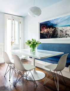 All white contemporary dining room table and chairs with blue bench seating and large wall art.