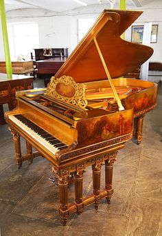 An art case,  1886, Steinway Model B grand piano with a gold case at Besbrode Pianos. Cabinet features hand paintings of cherubs and rural scenes of people playing musical instruments. Piano has ornately carved gate legs with four, ornately carved Corinthian pillars. Music desk has a beautiful scrolling filligree design with a central hand painted plaque.