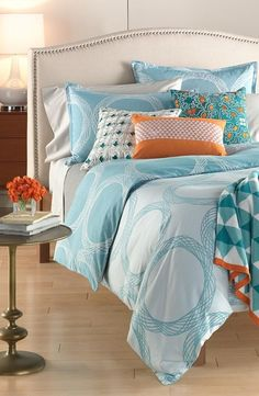 Create a fresh and bright bedroom with orange and blue tones.
