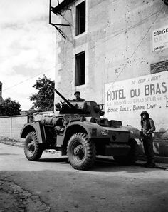 Belgian soldiers of the Belgian 1st Infantry Brigade, Free Belgian Forces, pose for a photograph with their British Daimler Armoured Car (Mk. II) following their liberation of the French village of Sallenelles during the Battle of Normandy. Sallenelles, Calvados, Lower Normandy, France. August 1944.