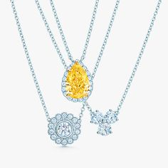 Pendants in platinum with diamonds, from left: Tiffany Enchant® flower, Tiffany Soleste® yellow diamond in 18k gold, Tiffany Aria.
