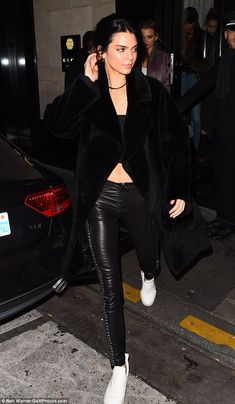 Model behaviour: She flaunted her enviably toned abs in a simple ribbed black crop top and slung a plush long-line fur coat over the top