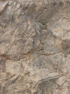 Rough rock cliff texture in brown color with cracking surface.