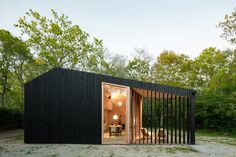 The building is clad externally in black-stained timber and features an irregular roof form that rises on one side to accommodate a loft-level sleeping area. Prefab Buildings, Timber Cabin, Timber Structure, Minimal Home, Roof Light, Black Exterior, Architect Design, Concrete Floors, Traditional House