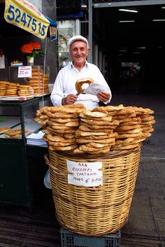 Koulouri vendor, Athens, Greece. Koluouri, a plain, circular bread topped with sesame seeds, tends to be the morning fare for most Greeks. It has evolved like bagels in the US, with new flavors in addition to the traditional plain. The bread must be eaten fresh, so it is best consumed early in the morning.