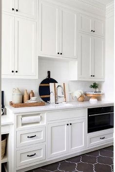 White shaker cabinets are fixed against white subway backsplash tiles over white shaker lower cabinets topped with a white quartz countertop and finished with oil rubbed bronze hardware. White shaker cabinets are fixed against white su White Shaker Cabinets, White Kitchen Cabinets, White Kitchens, Subway Backsplash, Backsplash Ideas, Kitchen Backsplash, Tudor Style Homes, U Bahn, Tudor House