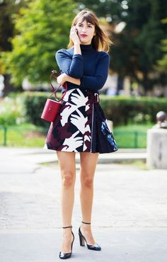 Jeanne Demas in a statement skirt paired with a turtleneck, mini red bag, and Valentino black heels