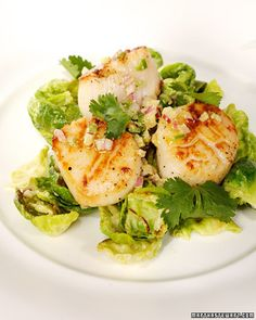 Sweet seared scallops rest on a bed of sauteed Brussels sprout leaves tossed in a spicy dressing. A mixture of chopped red onion, cilantro, and jalapeno pepper add the finishing touch.