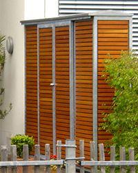 Bei diesen Reihenhäusern wurde statt der üblichen terrassentrennenden Wand ein moderner Geräteschrank als Sichtschutz gebaut. Sitzkissen, Rasenmäher oder Kinderspielzeug lassen sich gut darin verstauen.