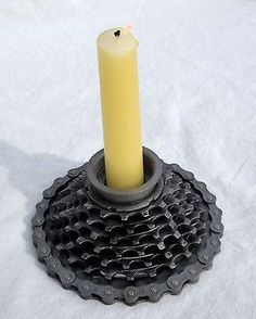 """This candle holder is made out of recycled bike parts. It is a great industrial-look style. It holds standard 7/8"""" size candles.  The gear base is roughly 5"""""""