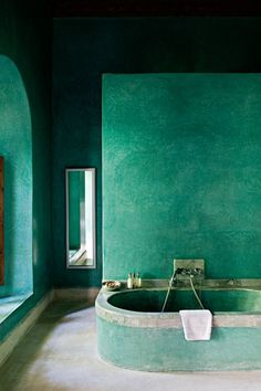 Gorgeous emerald green bathroom with Venetian plaster walls and a built-in soaking tub.