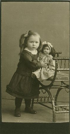 Antique photo of a little girl with her doll circa 1910.