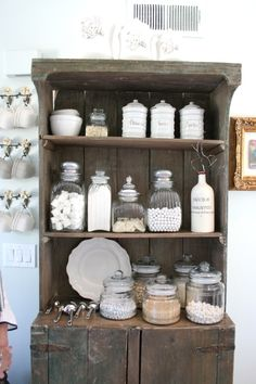 rustic kitchen hutch with white jars and accessories