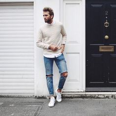 This combo of a nude cable knit sweater and blue distressed jeans will enable you to keep your off-duty style clean and simple. Round off this look with white low top sneakers. Shop this look on Lookastic: https://lookastic.com/men/looks/beige-cable-sweater-white-long-sleeve-shirt-blue-jeans/21193 — White Long Sleeve Shirt — Beige Cable Sweater — Blue Ripped Jeans — White Low Top Sneakers