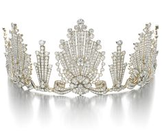 DIAMOND TIARA, 1950S.  Designed as a graduated series of radiating fans, each centring on a flower head and  foliate motif respectively, set with circular-, single- and rose-cut diamonds, inner circumference approximately  310mm, detachable, fitted tiara case.
