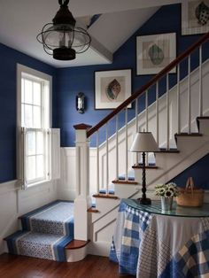 Coastal stairway with a fun hanging light and great shell wall art!