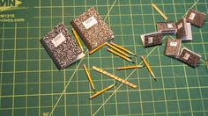 I created these tiny composition books for use in a baby book layout with a school day theme. They come complete with ruled paper and a red margin on the left hand side. The larger books are in 1:6 scale and the smaller books are in traditional 1:12 miniature scale. The pencils are toothpicks cut in half and painted. The rulers are coffee stirrers. The grid is in one inch squares so you can gauge the actual size of these minis.
