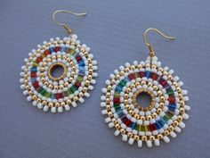 Medium beadwork hoop earrings made with 8/0 seed beads and 3mm cubes weaved with circular brick stitch technique. Fun and casual measuring 2 1/2long and 1 3/4wide. Materials: *8/0 opaque white miyuki seed beads* *8/0 galvanized starlight toho seed beads* *3mm rainbow mix cubes by miyuki* The beads are weaved around 10mm solid brass closed rings,earrings hang from raw brass earwires. *THANKS FOR LOOKING!*
