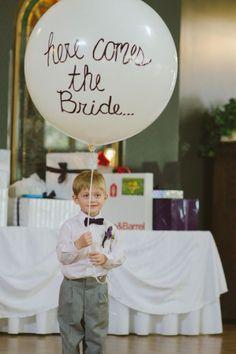 Idea de entrada de la novia, niño con globo aqui viene la novia - En la entrada de la novia, queda muy bien que un niño entre con un cartel muy divertido indicando la entrada de la novia.
