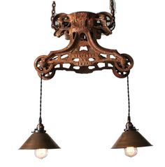A truly eye-catching creation for your dining space or foyer, this handcrafted piece is fashioned from an antique barn door pulley. The brass pendant