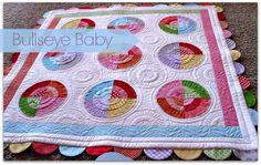 Bullseye Baby Quilt - I love the shadow quilting in the blank spaces.  Free tutorial.